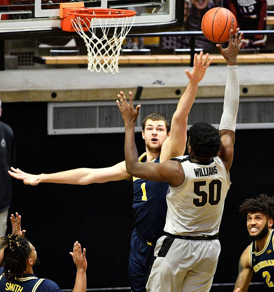 Michigan center Hunter Dickinson defends the shot by Purdue forward Trevion Williams during the second half at Mackey Arena in West Lafayette, Ind., Friday, Jan. 22, 2021.