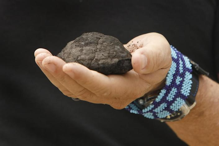 The Metals Company CEO Gerard Barron holds a dark rock brought up from the floor of the Pacific Ocean.