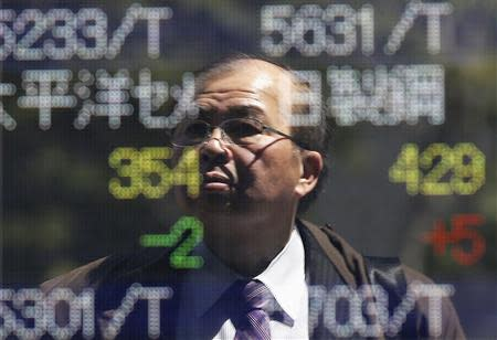 A man is reflected on an electronic stock quotation board outside a brokerage in Tokyo April 14, 2014. REUTERS/Issei Kato