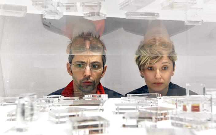 Artists Eva, right, and Franco Mattes look across their art work called 'Stolen Pieces' on display at the Carroll/Fletcher Gallery in London, Thursday, April 12, 2012. The exhibition opens to the public on April 13, and displays stolen fragments from works by a roll call of the 20th century's best known artists. (AP Photo/Kirsty Wigglesworth)