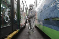 A worker wearing a protective suit sprays disinfectant as a precaution against the coronavirus at a bus garage in Seoul, South Korea, Wednesday, Feb. 26, 2020. The number of new virus infections in South Korea jumped again Wednesday and the U.S. military reported its first case among its soldiers based in the Asian country, with his case and many others connected to a southeastern city with an illness cluster. (AP Photo/Ahn Young-joon)