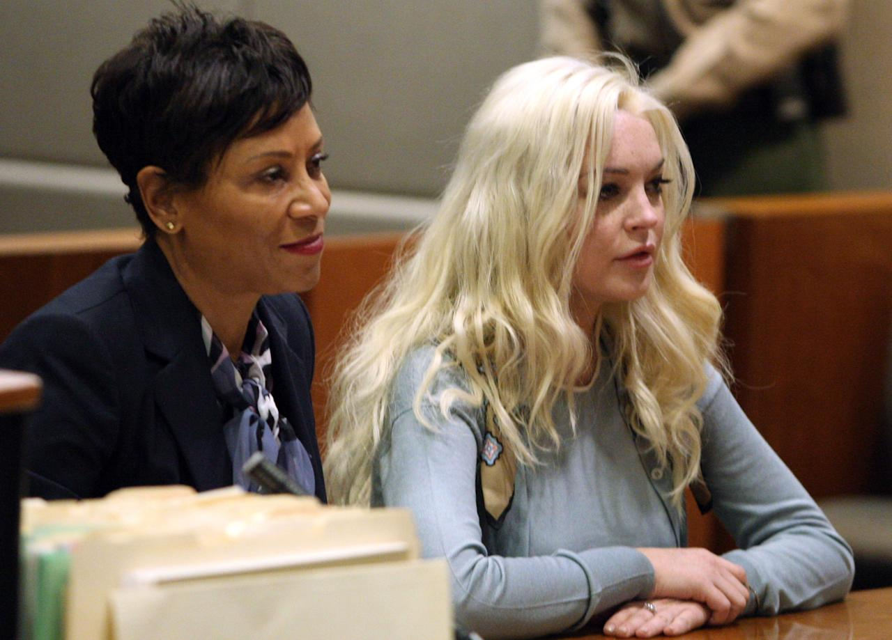 Lindsay Lohan, right, appears with her attorney Shawn Chapman Holley in Los Angeles Superior Court for a probation progress hearing Tuesday, Jan. 17, 2012. Superior Court Judge Stephanie Sautner told the actress she is on track to complete strict terms of her probation by the end of March. The 25-year-old is required to do cleanup duty at the morgue and attend therapy sessions. (AP Photo/Gary Friedman, Pool)