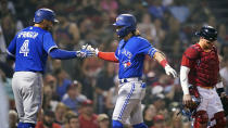 Toronto Blue Jays' Bo Bichette, center, is congratulated by George Springer (4) after his two-run home run off Boston Red Sox starting pitcher Nick Pivetta in the fifth inning of a baseball game at Fenway Park, Monday, July 26, 2021, in Boston. At right is Boston Red Sox catcher Christian Vazquez. (AP Photo/Charles Krupa)