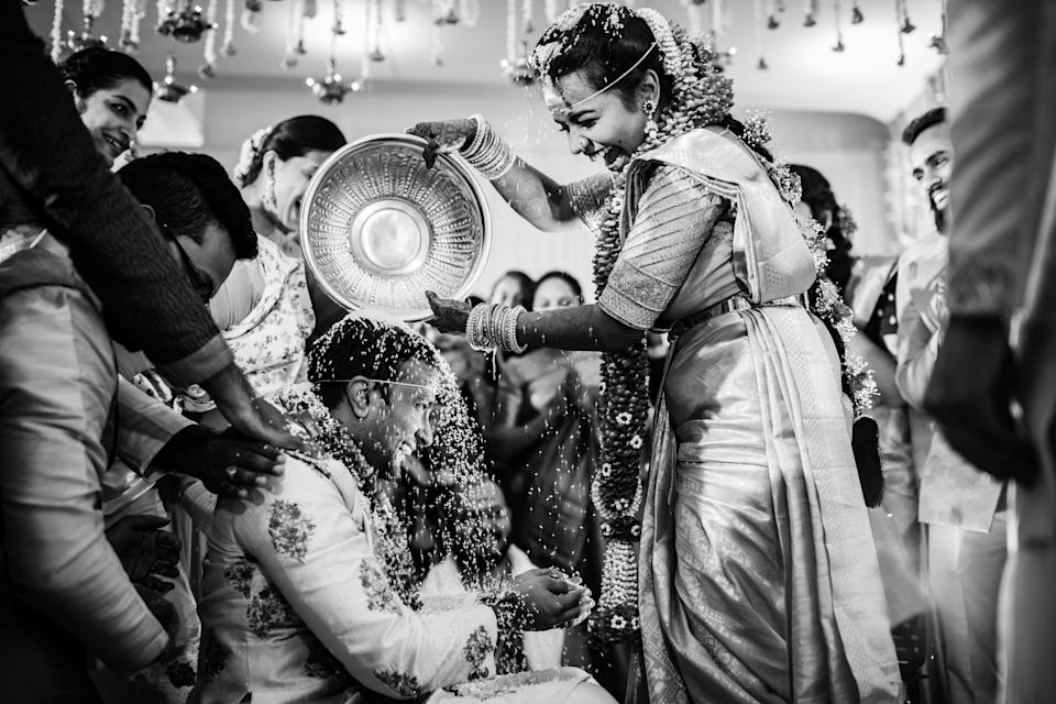 <p>A bride pours rice over her groom's head at a traditional Indian wedding. <em>[Photo: ANKITA ASTHANA / JUNEBUG WEDDINGS / CATERS]</em> </p>