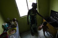 """Lady Laurentino, 74, show her almost empty pantry her home in the Jardim Gramacho favela of Rio de Janeiro, Brazil, Monday, Oct. 4, 2021. Laurentino who now cooks with firewood instead of gas because of the recent surge in prices, says that at night she hopes it doesn't rain. """"There is no other way, I use firewood. If, at night, I can heat up the food, but if it rains, I eat it cold."""" She says. (AP Photo/Silvia Izquierdo)"""