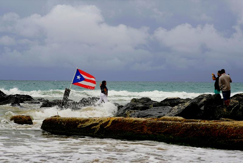 A woman poses for a photo backdropped by ocean waters and a Puerto Rican national flag, after the passing of Tropical Storm Dorian, in the Condado district of San Juan, Puerto Rico, Wednesday, Aug. 28, 2019.