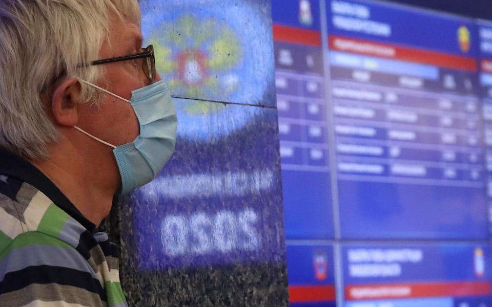 A man stands next to a screen displaying preliminary voting results - Sergei Fadeichev\\TASS via Getty Images