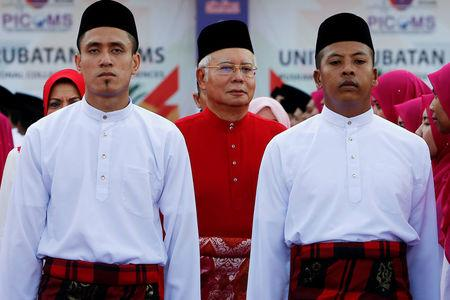 Malaysia's Prime Minister Najib Razak inspects an honour guard during the United Malays National Organization (UMNO) general assembly in Kuala Lumpur