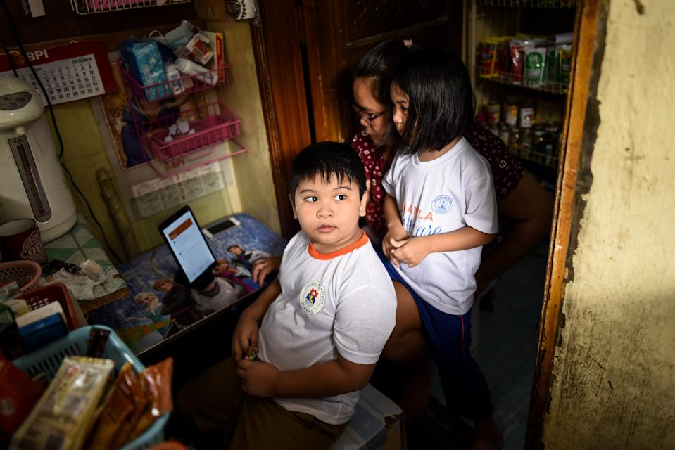 FILE PHOTO: A grade 2 student accompanied by his mother and sister waits for his online class to start at his family's store in front of their home in Manila, Philippines on October 7, 2020.(Photo: Lisa Marie David/NurPhoto via Getty Images)