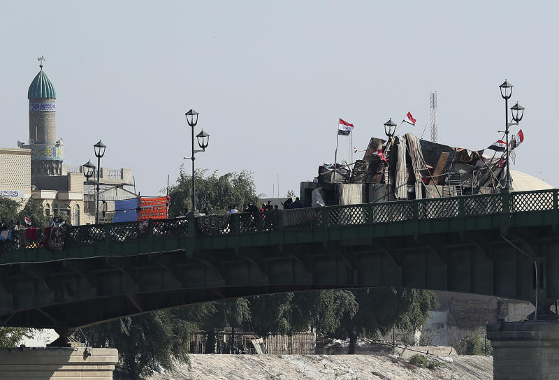 Anti-government protesters sit-in on barriers set up by security forces to close a bridge in Baghdad, Iraq, Tuesday, Nov.19, 2019. Anti-government protests have effectively cut Iraq's capital in half and citizens are increasingly relying on boats to ferry them to the other side of the river city, as standoffs between demonstrators and security forces have shut three key bridges connecting east and west Baghdad. (AP Photo/Hadi Mizban)