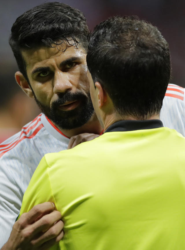 Spain's Diego Costa, left is spoken to by referee Andres Cunha from Uruguay after appearing to stand on the foot of Iran goalkeeper Ali Beiranvand on during the group B match between Iran and Spain at the 2018 soccer World Cup in the Kazan Arena in Kazan, Russia, Wednesday, June 20, 2018. (AP Photo/Sergei Grits)