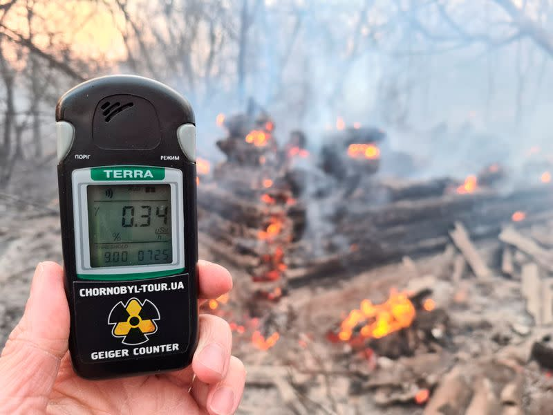 A geiger counter measures a radiation level at a site of fire burning in the exclusion zone around the Chernobyl nuclear power plant