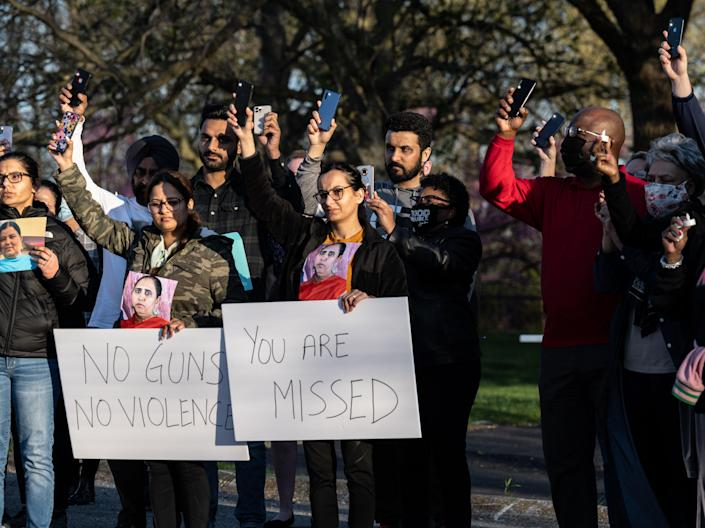 Families, coworkers, and government officials raise their cell phone flashlights during a vigil on April 17, 2021 in Indianapolis, Indiana. (Getty Images)