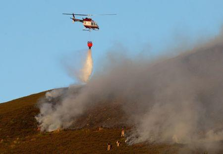 <p>Another helicopter drops water as firefighters tackle the blaze (REUTERS/Phil Noble) </p>