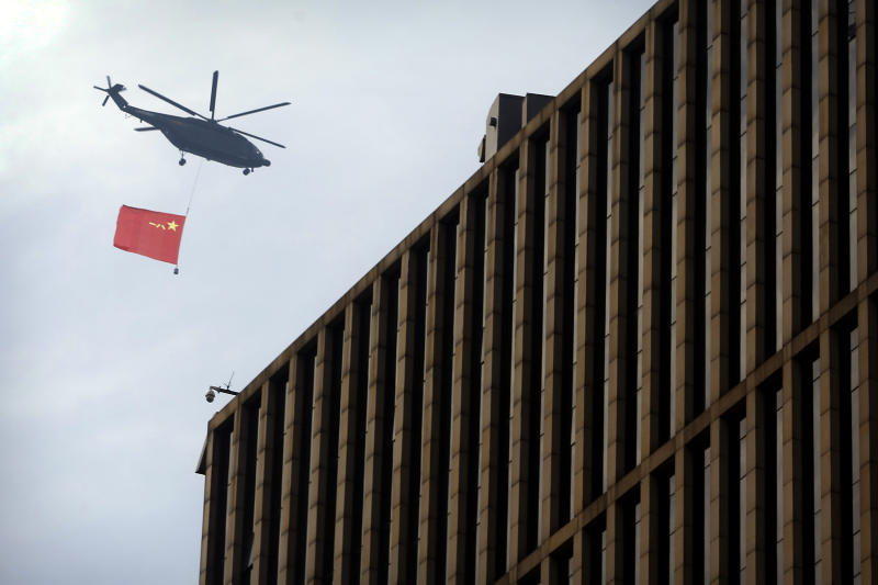 A helicopter carrying the flag of China's People's Liberation Army (PLA) flies above the central business district in Beijing, Sunday, Sept. 15, 2019. Many of the streets in the central part of China's capital were shut down this weekend for a rehearsal for what is expected to be a large military parade on Oct. 1 to commemorate the 70th anniversary of Communist China. (AP Photo/Mark Schiefelbein)