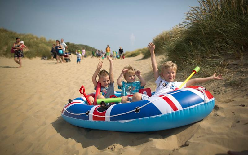 Children enjoy the hot weather on Camber Sands beach in Sussex  - Christopher Pledger