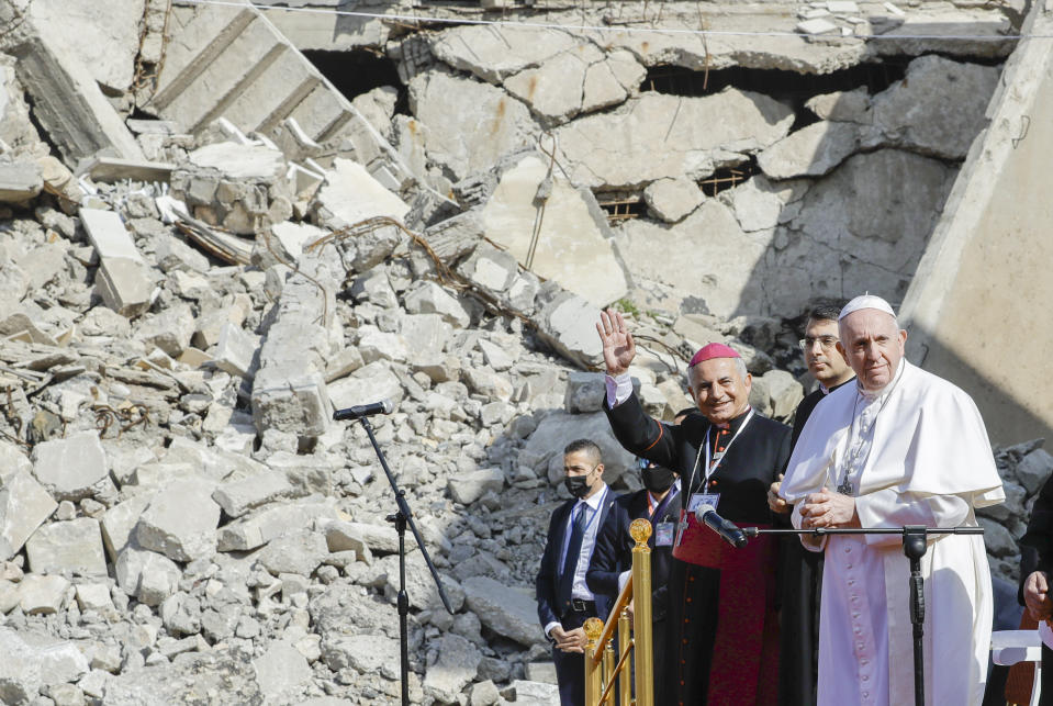 Mosul and Aqra Archbishop Najib Mikhael Moussa, left, waves as he stands next to Pope Francis at the start of a gathering to pray for the victims of war at Hosh al-Bieaa Church Square, in Mosul, Iraq, once the de-facto capital of IS, Sunday, March 7, 2021. The long 2014-2017 war to drive IS out left ransacked homes and charred or pulverized buildings around the north of Iraq, all sites Francis visited on Sunday. (AP Photo/Andrew Medichini)