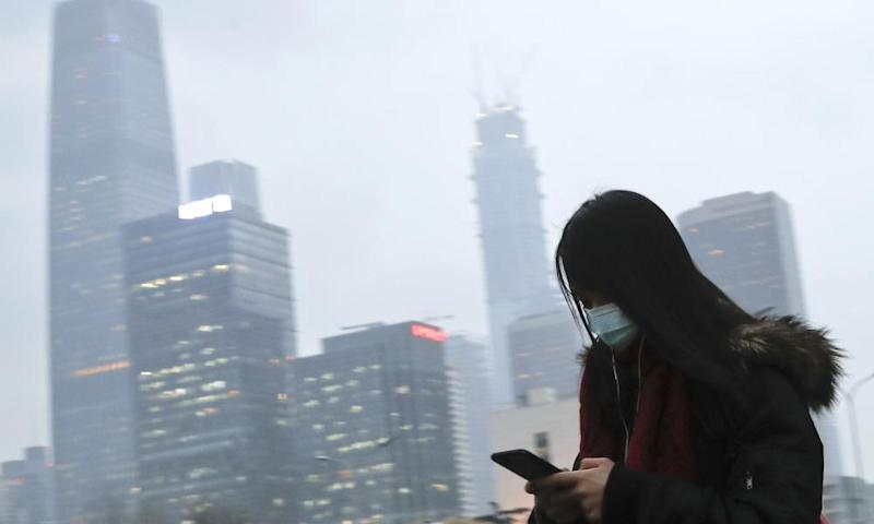 A woman wearing a mask walks to a subway station in Beijing in heavy smog.