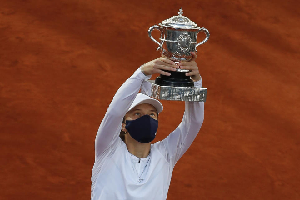 FILE - Poland's Iga Swiatek lifts the trophy after winning the final match of the French Open tennis tournament against Sofia Kenin of the U.S., 6-4, 6-1, at Roland Garros stadium in Paris, France, in this Saturday, Oct. 10, 2020, file photo. Swiatek won her first Grand Slam title at the 2020 French Open, winning every set she played. (AP Photo/Alessandra Tarantino, File)