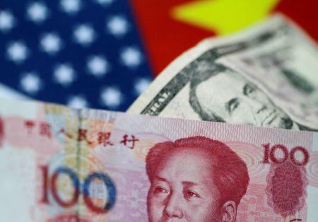 FILE PHOTO: U.S. Dollar and China Yuan notes are seen in this picture illustration June 2, 2017. REUTERS/Thomas White/Illustration/File Photo
