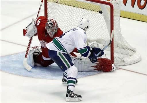 Vancouver Canucks right wing Alex Burrows (14) scores the winning goal against the Detroit Red Wings goalie Jimmy Howard (35) in a shootout during an NHL hockey game in Detroit, Thursday, Feb. 23, 2012. Vancouver 4-3. (AP Photo/Paul Sancya)