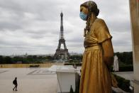 FILE- In this file photo dated Monday, May 4, 2020, a statue wears a mask along Trocadero square close to the Eiffel Tower in Paris. Britain will require all people arriving from France to isolate for 14 days - an announcement that throws the plans of tens of thousands of holiday makers into chaos. The government said late Thursday Aug. 13, 2020 that France is being removed from the list of nations exempted from quarantine requirements because of a rising number of coronavirus infections, which have surged by 66% in the past week.(AP Photo/Christophe Ena, File)