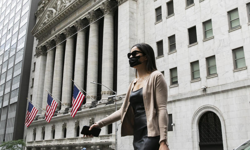 A woman wearing a mask passes the New York Stock Exchange, Tuesday, June 30, 2020, during the coronavirus pandemic. (AP Photo/Mark Lennihan)