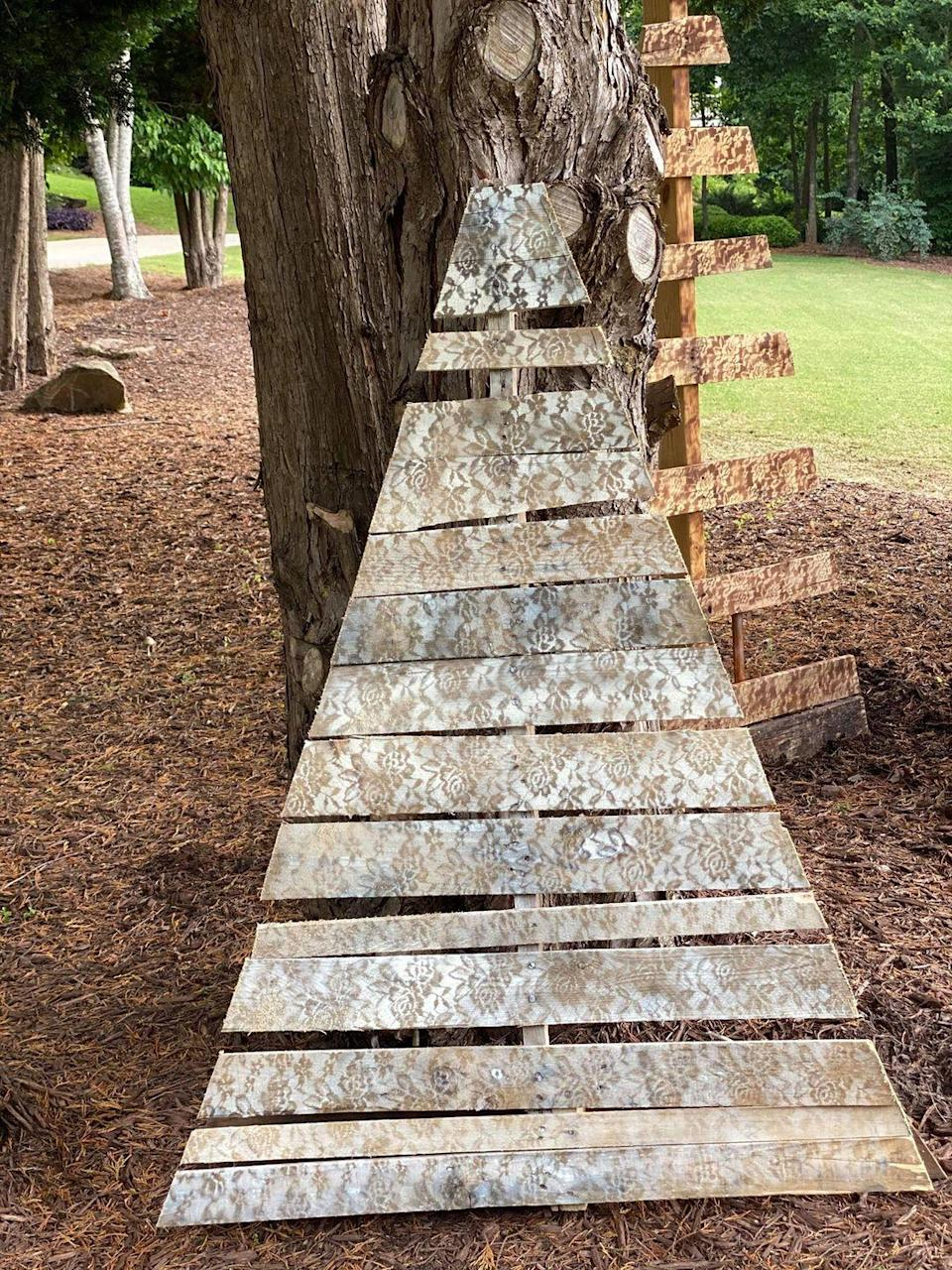 """<p>Believe it or not, all you need to create a lace look on your pallet tree is lace fabric and a can of spray paint. Lay the lace on your tree, paint over it, and presto! When you pull off the fabric you'll have a lace pattern left on your tree.</p><p><strong>Get the tutorial at <a href=""""https://theshabbytree.com/diy-pallet-tree/"""" rel=""""nofollow noopener"""" target=""""_blank"""" data-ylk=""""slk:The Shabby Tree"""" class=""""link rapid-noclick-resp"""">The Shabby Tree</a>.</strong></p><p><a class=""""link rapid-noclick-resp"""" href=""""https://www.amazon.com/Lace-Realm-Raschel-Vintage-Decorations/dp/B09312RMJZ/ref=sr_1_56_sspa?tag=syn-yahoo-20&ascsubtag=%5Bartid%7C10050.g.23322271%5Bsrc%7Cyahoo-us"""" rel=""""nofollow noopener"""" target=""""_blank"""" data-ylk=""""slk:SHOP LACE"""">SHOP LACE</a><br></p>"""