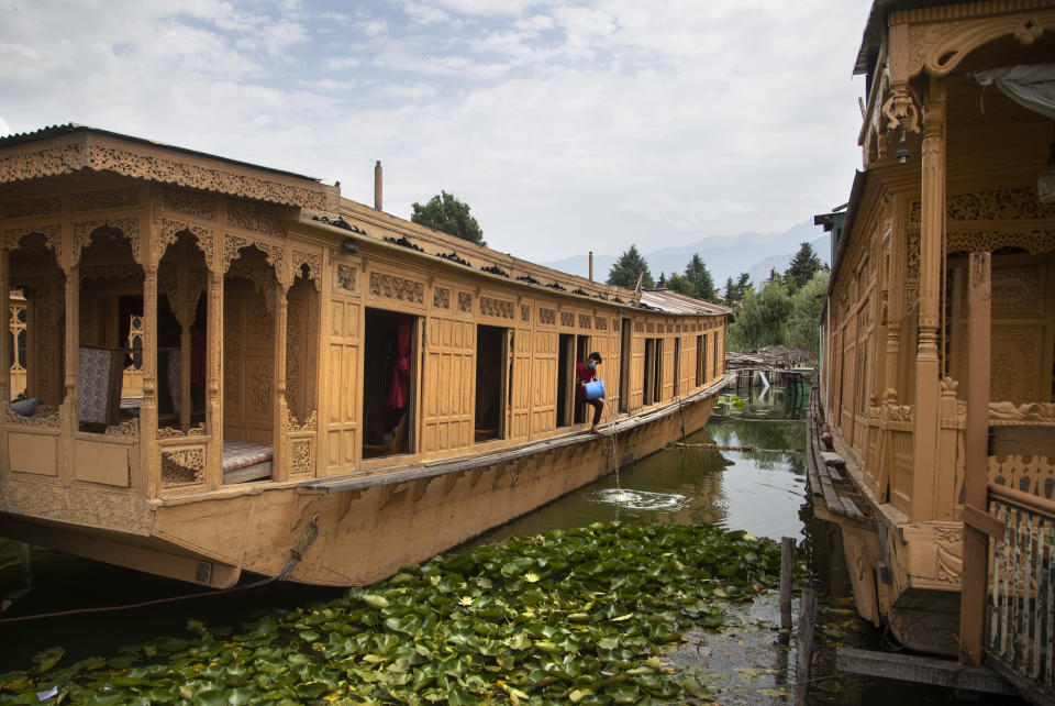Kashmiri man Illiyas Ahamad cleans an unoccupied houseboat at Nigeen Lake during lockdown to stop the spread of the coronavirus in Srinagar, Indian controlled Kashmir, July 16, 2020. Indian-controlled Kashmir's economy is yet to recover from a colossal loss a year after New Delhi scrapped the disputed region's autonomous status and divided it into two federally governed territories. (AP Photo/Mukhtar Khan)