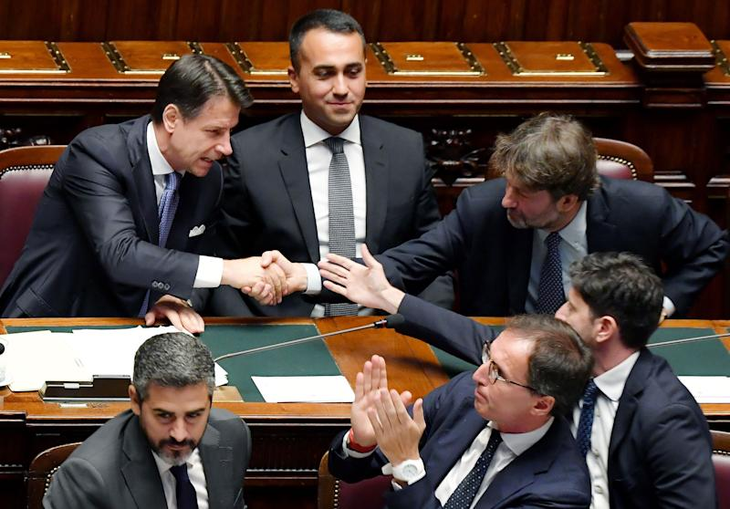 Italy's Prime Minister Giuseppe Conte (L) shakes hand with Italy's Culture minister Dario Franceschini (R) and Italy's Health Minister Roberto Speranza (Bottom R) as Italy's Foreign Minister Luigi Di Maio (Top C), Italy's Minister of Regional Affairs Francesco Boccia (Bottom C) and Italy's Secretary of the Council of Ministers Riccardo Fraccaro (Bottom L) look on after Conte delivered a speech on September 9, 2019 during the new government confidence vote at the lower house of parliament in Rome. (Photo by Andreas SOLARO / AFP) (Photo credit should read ANDREAS SOLARO/AFP via Getty Images) (Photo: ANDREAS SOLARO via Getty Images)