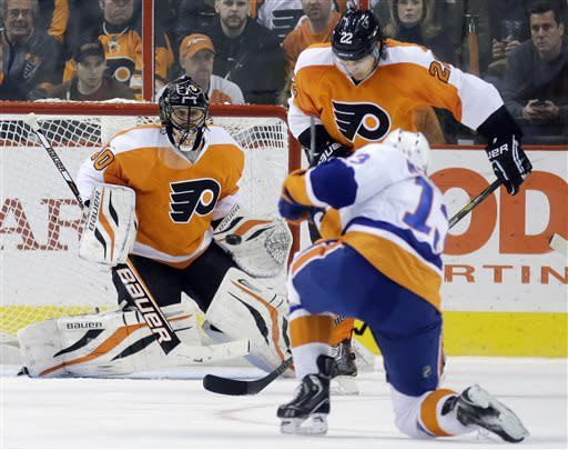 New York Islanders' Colin McDonald, right, tries to get a shot past Philadelphia Flyers' Ilya Bryzgalov, left, of Russia, and Flyers' Luke Schenn during the second period of an NHL hockey game, Thursday, March 28, 2013, in Philadelphia. (AP Photo/Matt Slocum)