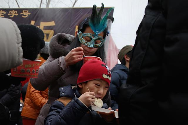 BEIJING, CHINA - FEBRUARY 11: Beijing residents eat steamed stuffed bun at a Spring Festival Temple Fair for celebrating Chinese Lunar New Year of Snake on February 11, 2013 in Beijing, China. The Chinese Lunar New Year of Snake also known as the Spring Festival, which is based on the Lunisolar Chinese calendar, is celebrated from the first day of the first month of the lunar year and ends with Lantern Festival on the Fifteenth day. (Photo by Feng Li/Getty Images)