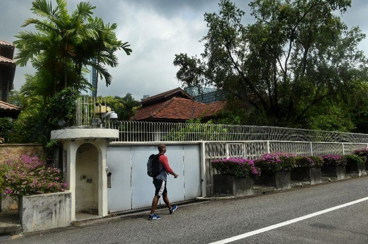 A man walks past 38 Oxley Road, the home for Singapore's late prime minister Lee Kuan Yew. (PHOTO: AFP)