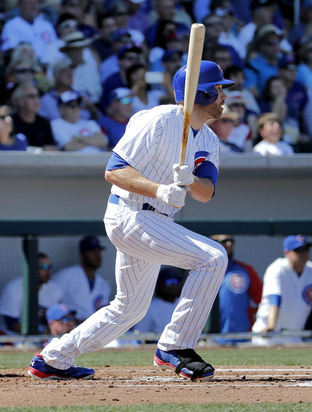 Chicago Cubs' Nate Schierholtz watches his RBI sacrifice fly during the first inning of a spring training baseball game against the Cincinnati Reds, Saturday, March 22, 2014, in Mesa, Ariz. (AP Photo/Matt York)