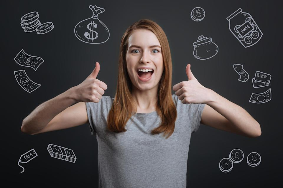 Young woman with thumbs up in front of a chalkboard with drawings of money