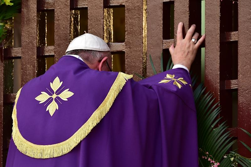 "Pope Francis symbolically opens a gate to peace at Bangui Cathedral in the Central African Republic on November 29, 2015, appealing during a landmark mass to warring factions and urging them to ""lay down these instruments of death"" (AFP Photo/Giuseppe Cacace)"