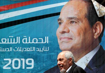 A man walks in front of a banner depicting Egyptian President Abdel Fattah al-Sisi before the upcoming referendum on constitutional amendments in Cairo, Egypt April 16, 2019. REUTERS/Mohamed Abd El Ghany