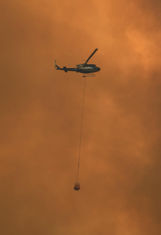 A helicopter drops water on a homestead as bushfires impact on farmland near the small town of Nana Glen, some 600kms north of Sydney on November 12, 2019. - Bushfires reached within kilometres (miles) of Sydney's city centre prompting firefighting planes to spray red retardant over trees and houses in a northern suburb. (Photo by WILLIAM WEST / AFP) (Photo by WILLIAM WEST/AFP via Getty Images)