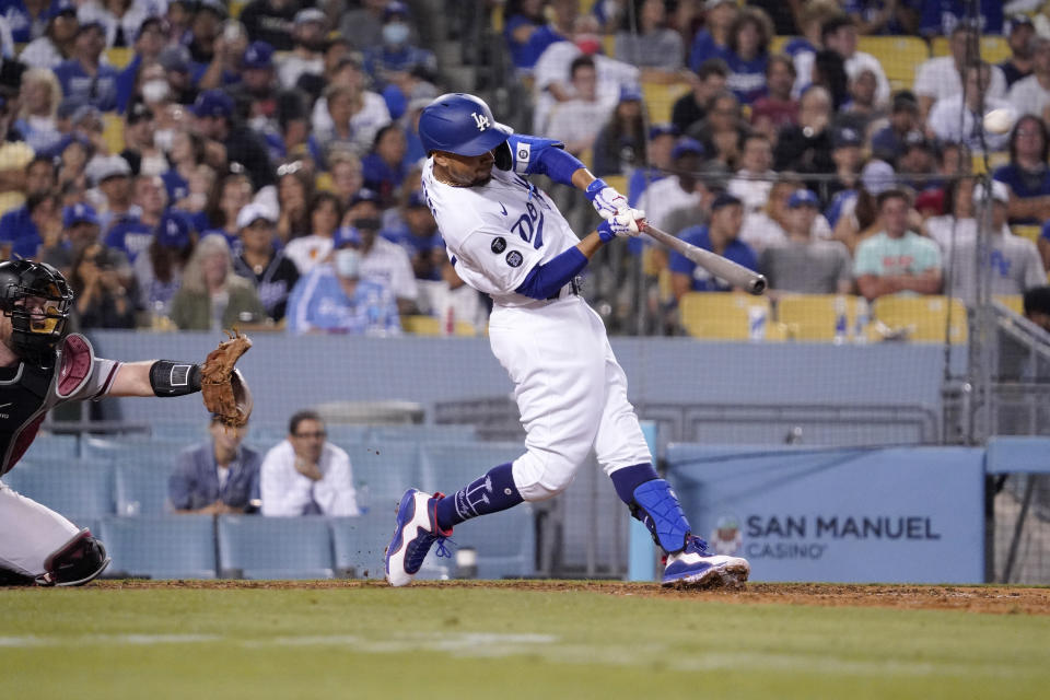 Los Angeles Dodgers' Mookie Betts, right, hits a grand slam as Arizona Diamondbacks catcher Bryan Holaday watches during the seventh inning of a baseball game Saturday, July 10, 2021, in Los Angeles. (AP Photo/Mark J. Terrill)