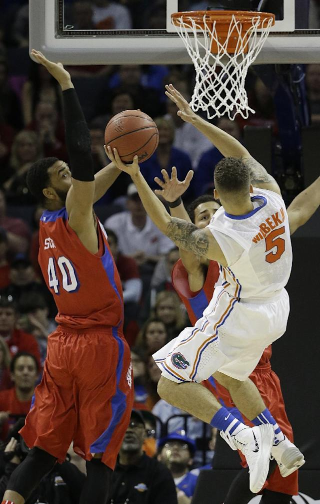 Florida guard Scottie Wilbekin (5) shoots against Dayton forward/center Devon Scott (40) during the second half in a regional final game at the NCAA college basketball tournament, Saturday, March 29, 2014, in Memphis, Tenn. (AP Photo/Mark Humphrey)