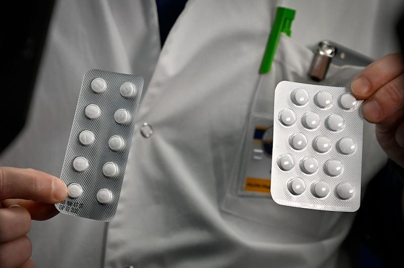 Medical staff shows packets of a Nivaquine, tablets containing chloroquine and Plaqueril, tablets containing hydroxychloroquine, drugs that have shown signs of effectiveness against coronavirus. (Photo by GERARD JULIEN/AFP via Getty Images)