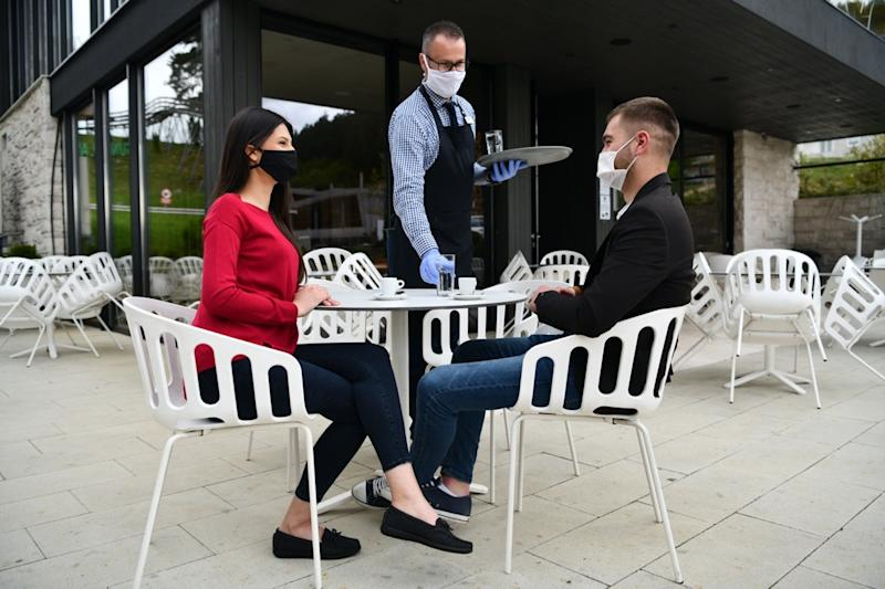 Waiter with protective medical mask and gloves serving guest with coffee at an outdoor bar café or restaurant new normal concept reopening after quarantine