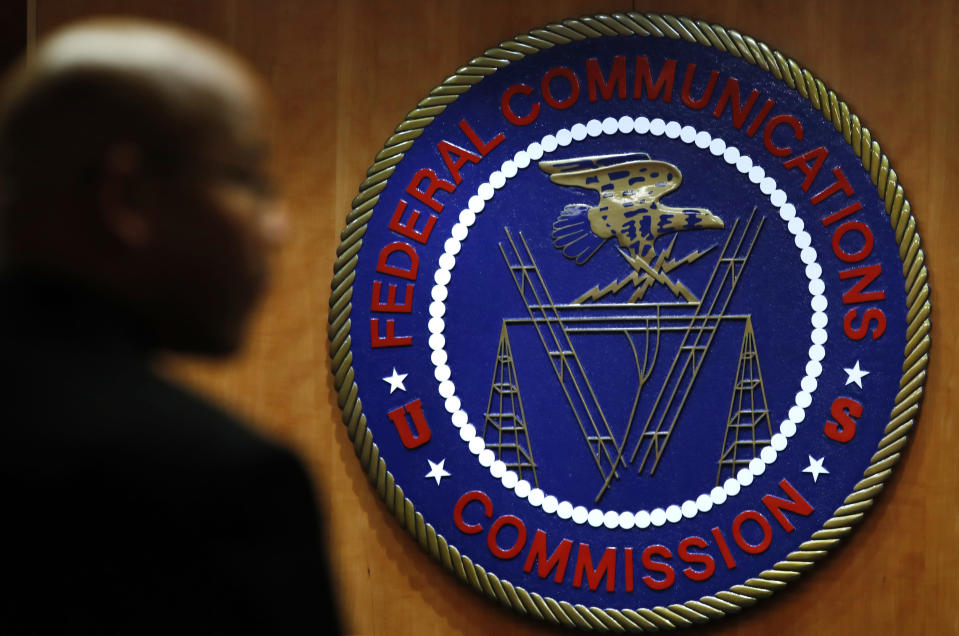 FILE- This Dec. 14, 2017, file photo, shows the seal of the Federal Communications Commission (FCC) before a meeting in Washington. Congressional leaders and a media accountability organization are urging the Federal Communications Commission to examine how policy decisions have disparately harmed Black people and other communities of color, according to a letter sent Tuesday, June 29, 2021, to the acting FCC chair. (AP Photo/Jacquelyn Martin, File)