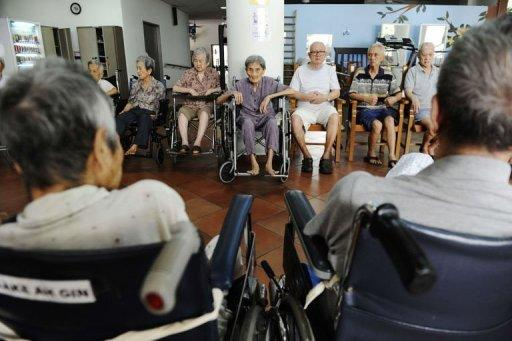 Elderly residents wait for their turn for morning exercises at a nursing home in Singapore. (AFP)