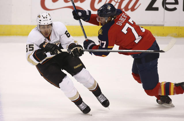 Anaheim Ducks' Emerson Etem (65) and Florida Panthers' Tom Gilbert (77) chase the puck during the first period of an NHL hockey game in Sunrise, Fla., Tuesday, Nov. 12, 2013. (AP Photo/J Pat Carter)