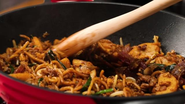Frying char kway teow in pan with wooden spatula