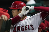 Los Angeles Angels designated hitter Shohei Ohtani (17) warms up in the dugout during the seventh inning of a baseball game against the Oakland Athletics Friday, Sept. 17, 2021, in Anaheim, Calif. (AP Photo/Ashley Landis)