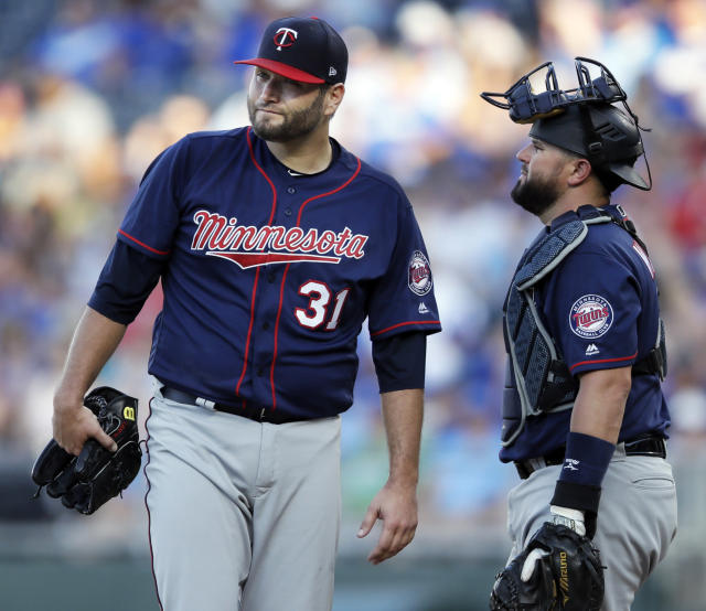 Minnesota Twins starting pitcher Lance Lynn (31) and catcher Bobby Wilson, right, talk after the Kansas City Royals loaded the bases during the third inning of a baseball game at Kauffman Stadium in Kansas City, Mo., Saturday, July 21, 2018. (AP Photo/Orlin Wagner)