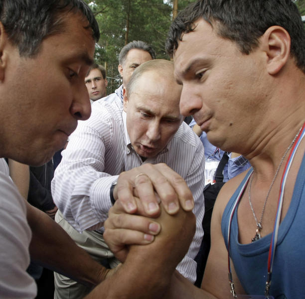 FILE - In this Monday, Aug. 1, 2011 file photo, Vladimir Putin, then Russian prime minister, center, tries to judge arm wrestling during his visits in the Seliger youth educational forum near Lake Seliger, some 450 kilometres (281 miles) northwest of Moscow, in the Tver region, Russia. An Associated Press-GfK poll has shown that 60 percent of Russians still maintain a favorable opinion of Putin, who won a third presidential term in March's election despite massive protests in Moscow against his rule. (AP Photo/Mikhail Metzel,file)