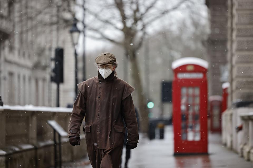 TOPSHOT - A man wearing a face mask because of the coronavirus pandemic walks in the street in London on February 8, 2021. (Photo by Tolga Akmen / AFP) (Photo by TOLGA AKMEN/AFP via Getty Images)